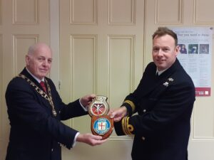 Photograph of Mayor of Cowes exchanging commemorative shields with the Commanding Officer of HMS Ledbury